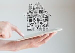 Dem Smart Home gehört die Zukunkft. Zu sehen ist ein Tablet, auf dem sich Steurungssymbole befinden, die die Form eines Hauses bilden.